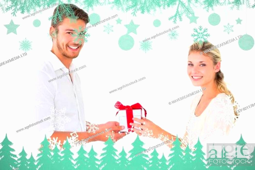 Stock Photo: Composite image of attractive young couple holding a gift.