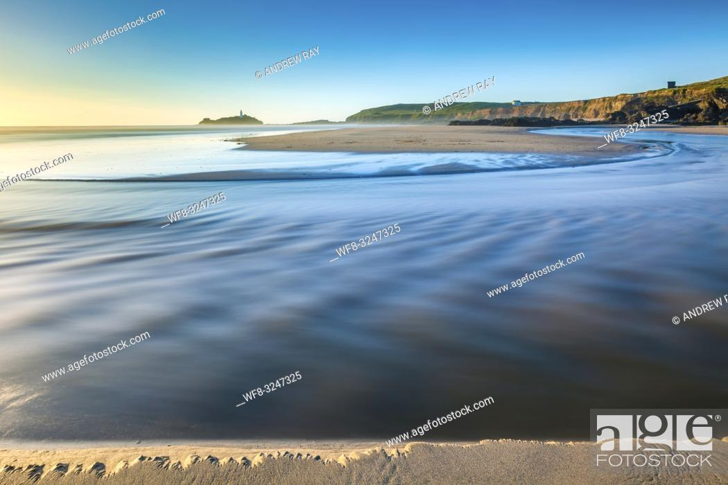 Stock Photo: The river on Gwithian Beach in Cornwall, captured shortly before sunset with Godrevy Lighthouse in the distance.