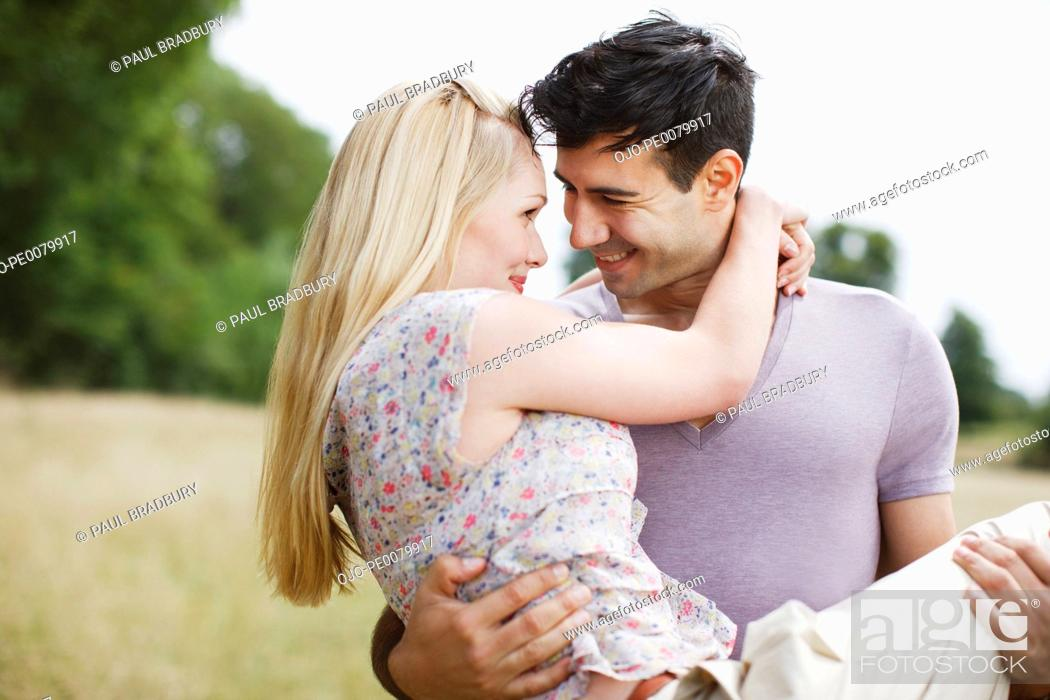 Stock Photo: Man carrying woman in rural field.