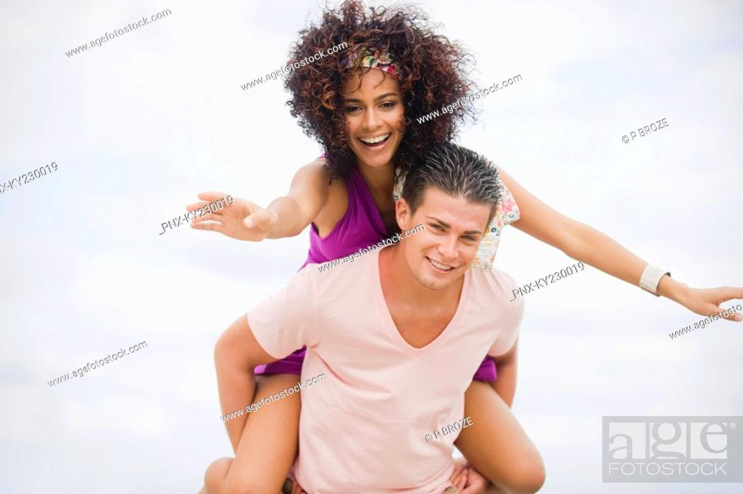 Stock Photo: Man giving woman piggyback ride on the beach.