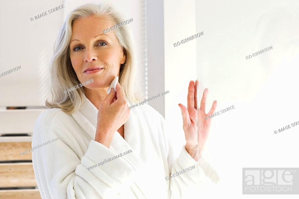 Stock Photo: Middle aged woman cleansing face with cotton pad.