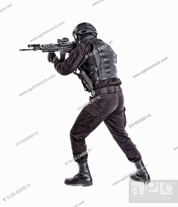 Imagen: Police anti terrorism squad fighter, SWAT team shooter ready for fight, moving forward with wariness, keeping weapon ready for shoot.