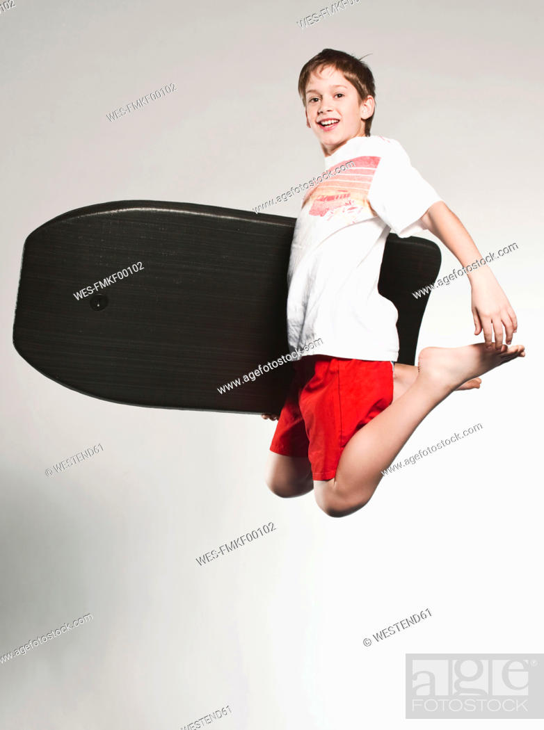 Stock Photo: Boy 12-13 jumping with boogie board, smiling, portrait.