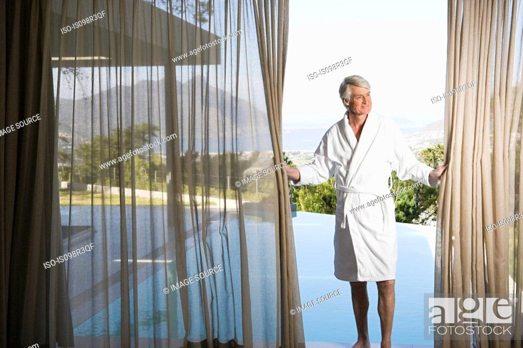 Stock Photo: Middle aged man in robe pulling back poolside curtains.