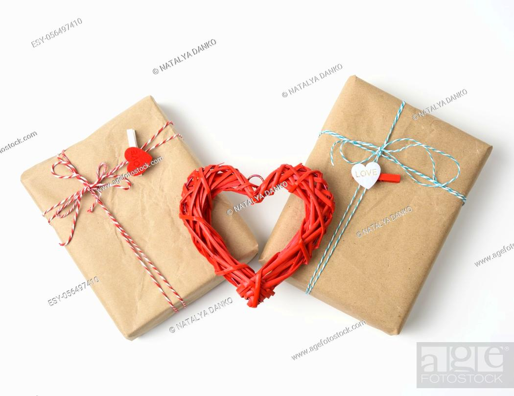 Stock Photo: wrapped gifts in brown paper and a red wicker heart on a white background, top view. Valentine's Day surprise.