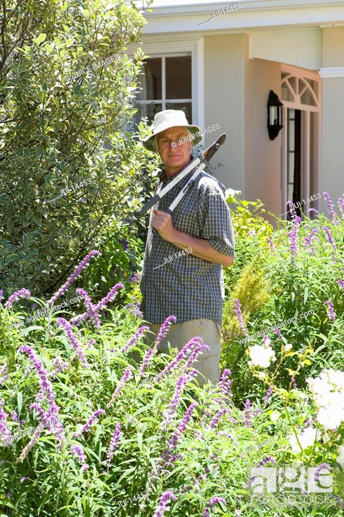Stock Photo: Senior man in garden with shears, portrait.