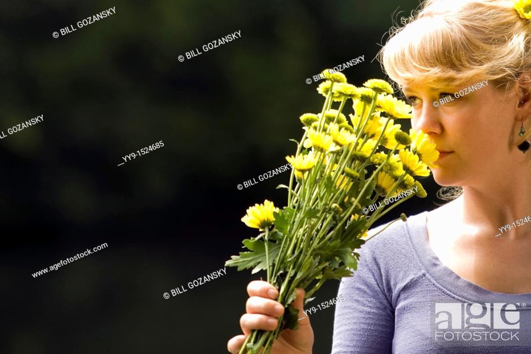 Stock Photo: Woman holding yellow flowers - Cedar Mountain, North Carolina, USA.