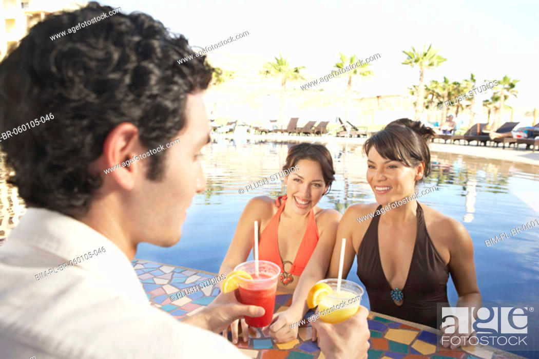 Stock Photo: Two Hispanic women getting drinks at a hotel pool bar, Los Cabos, Mexico.