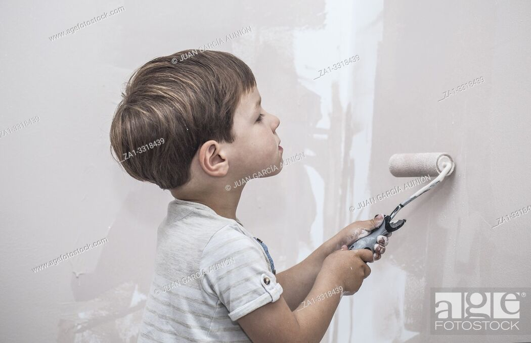 Stock Photo: 3 years cute little boy with paint roller in hand. Kids Helping House Chores concept.
