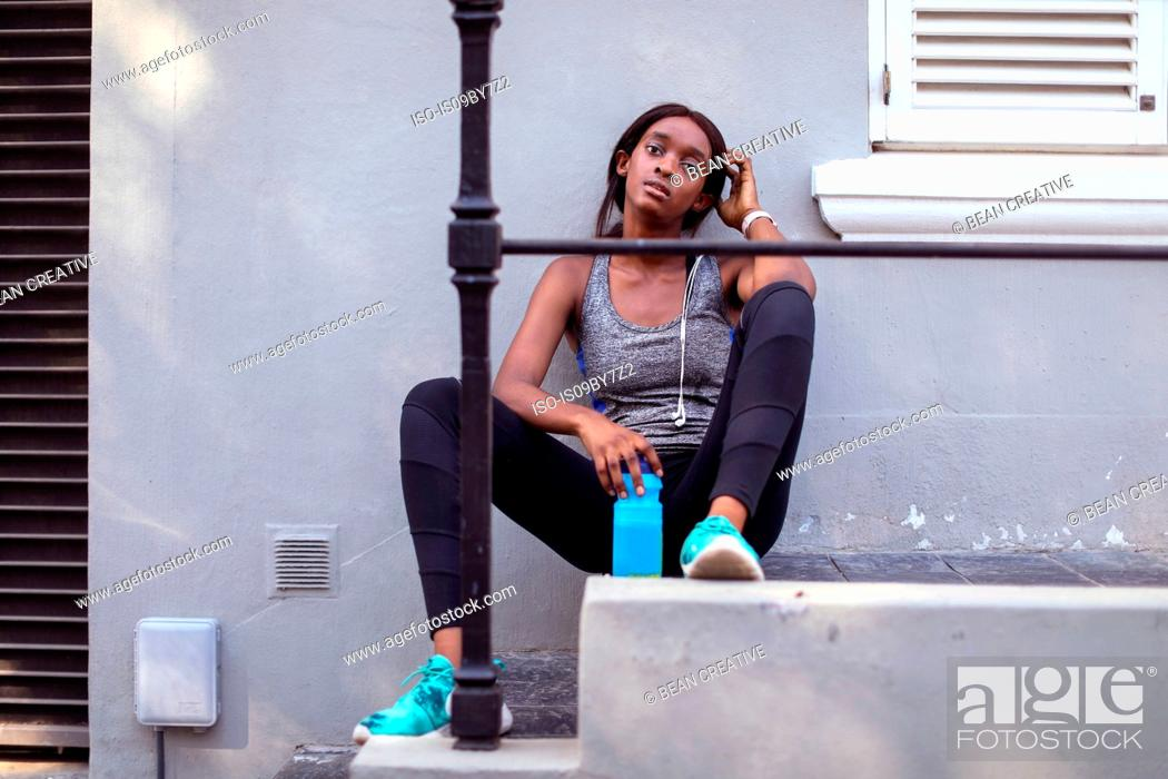 Stock Photo: Young female runner sitting on city sidewalk stairs, portrait.