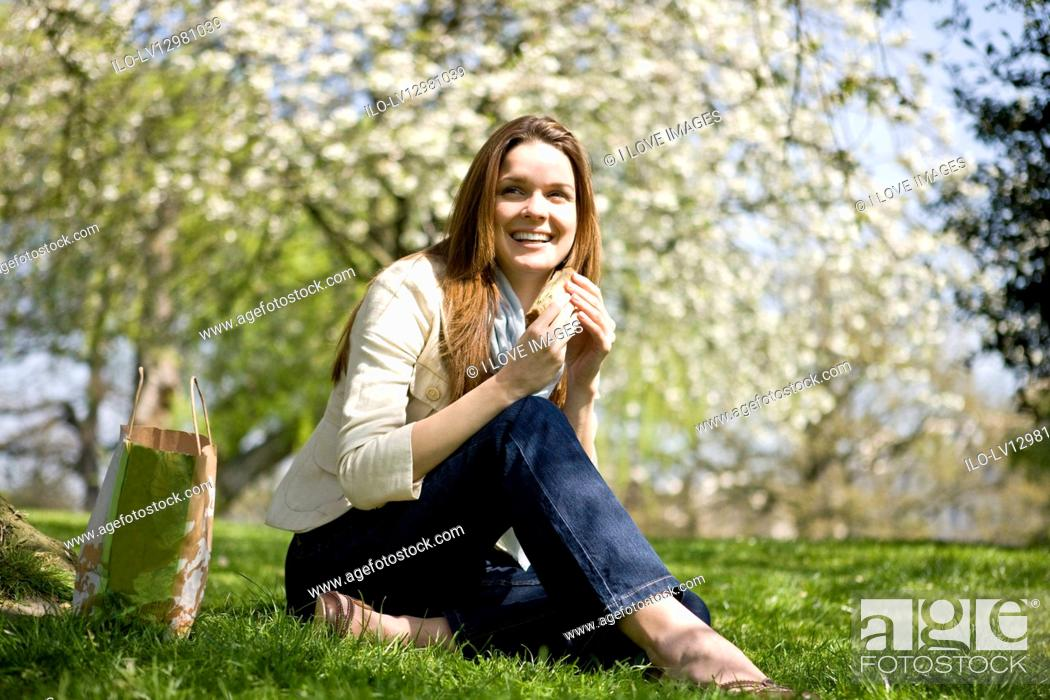 Stock Photo: A young woman eating a sandwich, outdoors.