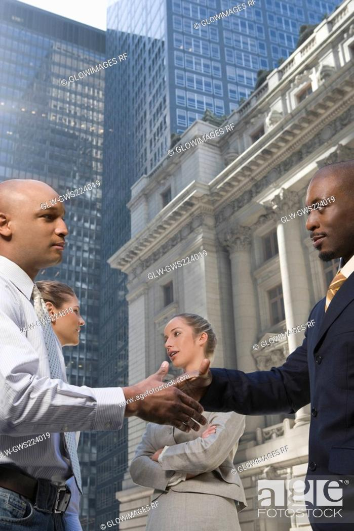 Stock Photo: Side profile of two businessmen shaking hands with two businesswomen smiling.