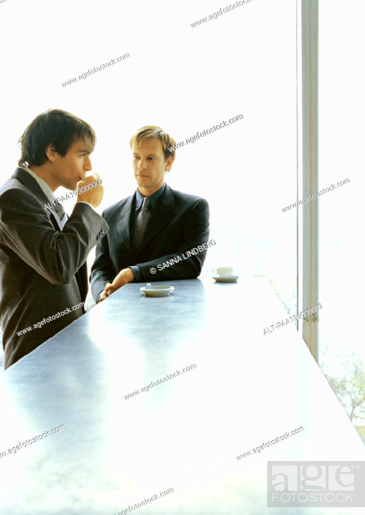 Stock Photo: Businessmen standing together, drinking coffee.