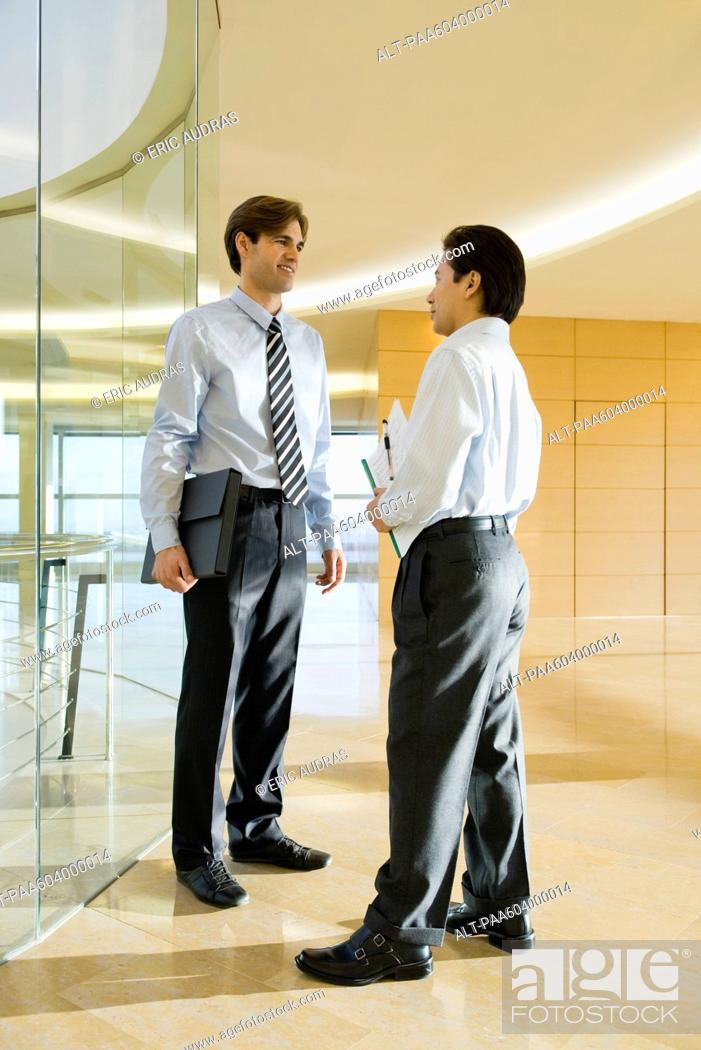 Stock Photo: Businessmen talking in corridor.