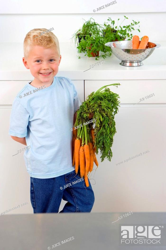 Stock Photo: Boy with bunch of carrots in kitchen, smiling, portrait, elevated view.