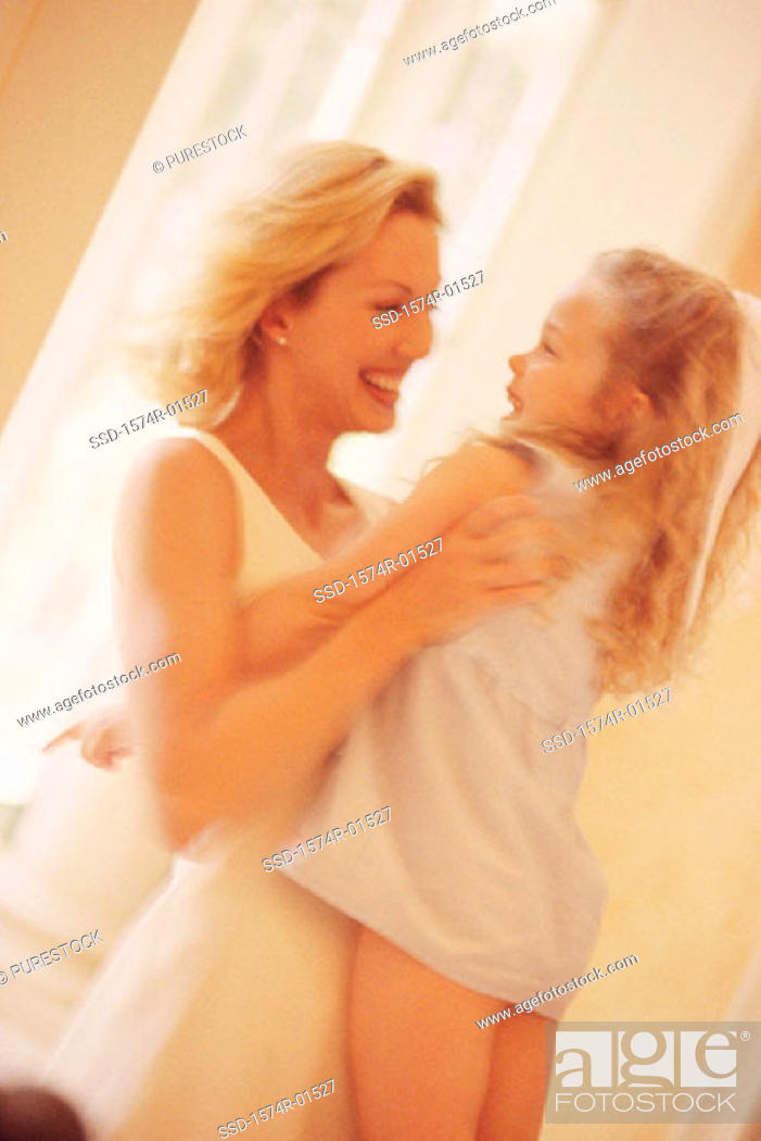 Stock Photo: Young woman lifting up her daughter.