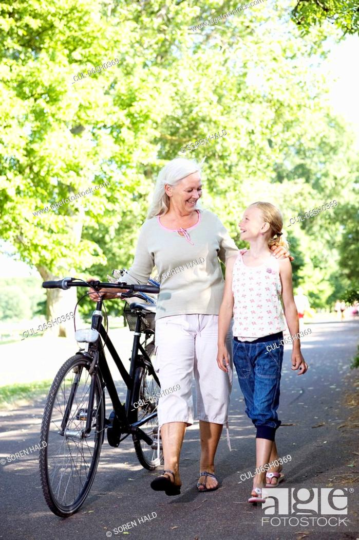 Stock Photo: Grandmother with granddaughter and bike.