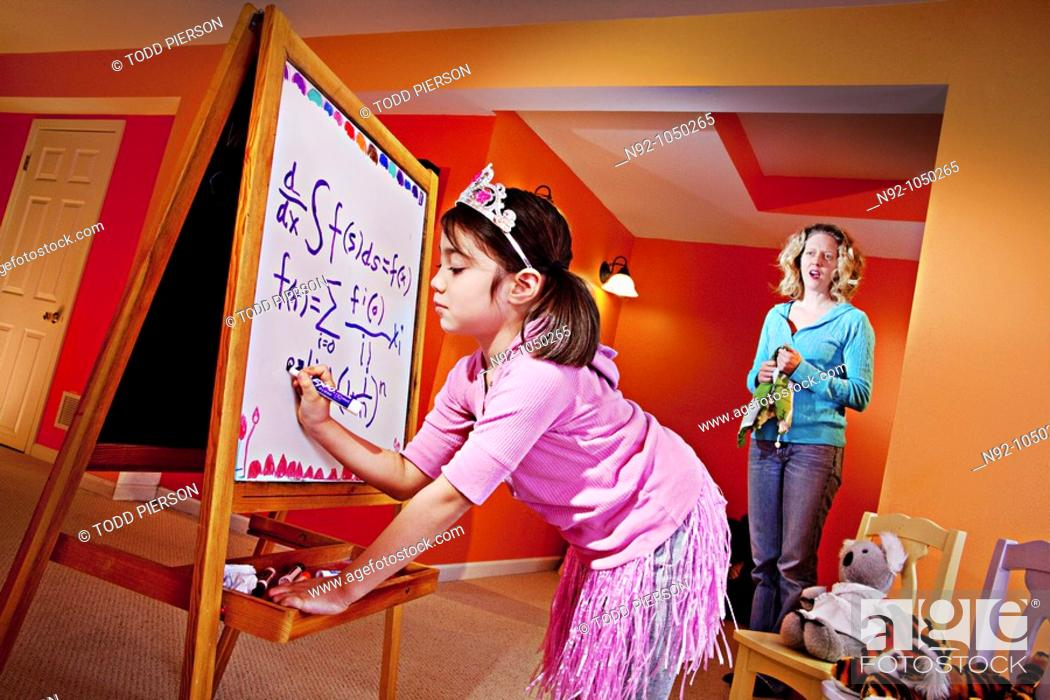 Stock Photo: Little girl, age 6 writing on board and mom standing by in awe.