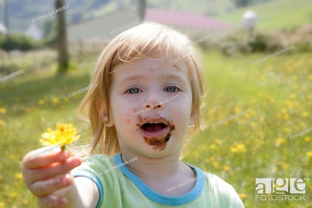 Photo de stock: Adorable little girl eating chocolate outdoor field.