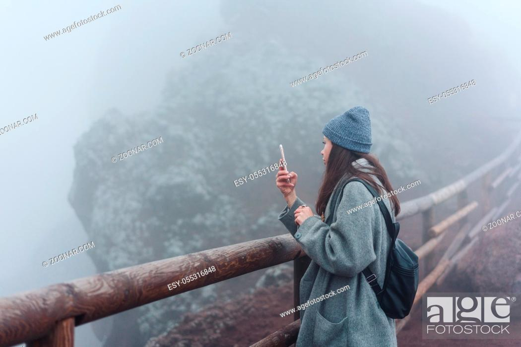 Photo de stock: Girl climbs the path to the mountain and taking pictures on the phone.