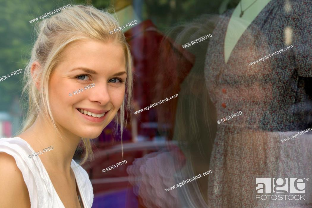 Stock Photo: Germany, North Rhine Westphalia, Cologne, Young woman at window shopping, smiling, portrait.