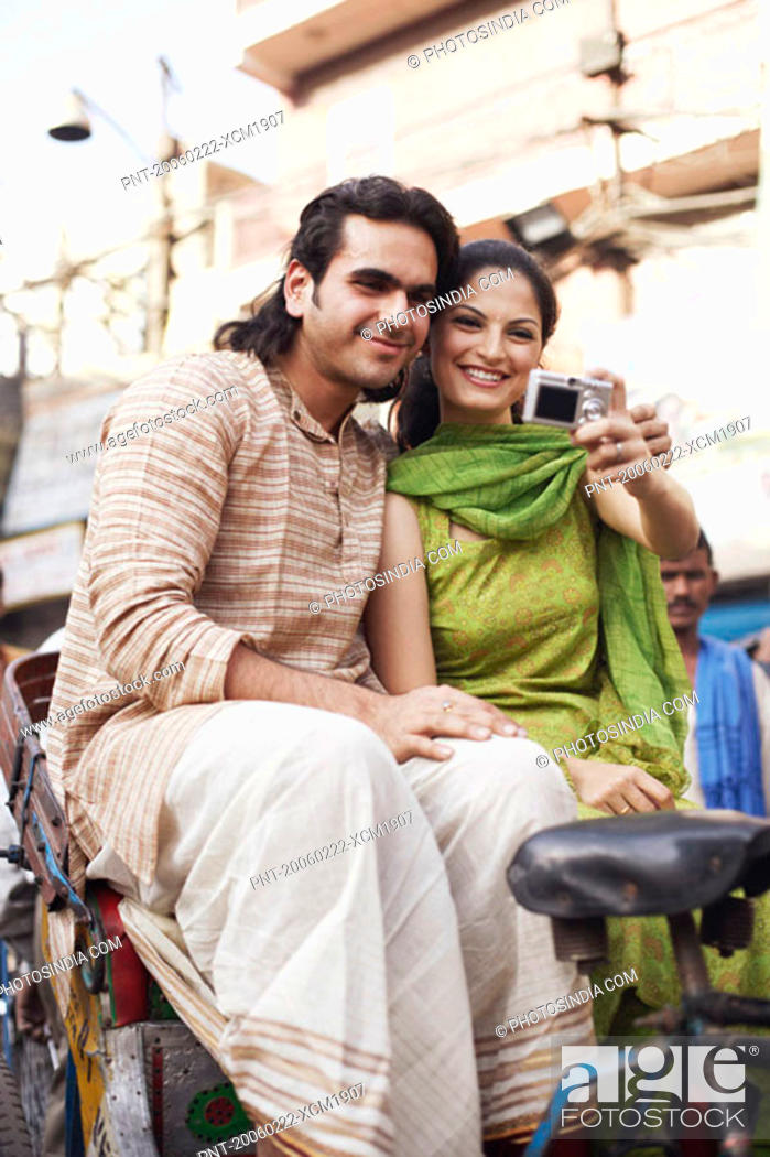 Stock Photo: Young couple sitting in a rickshaw and taking a photograph of themselves.