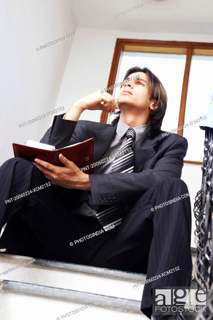 Stock Photo: Low angle view of a businessman sitting on the staircase holding a personal organizer.