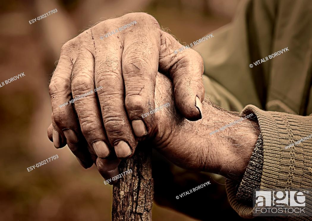 Stock Photo: Dramatic photo of an elderly man hand holding a staff.