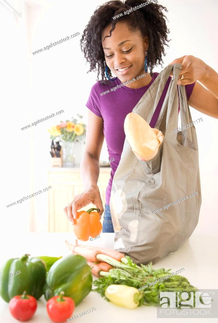 Stock Photo: African woman unpacking groceries.