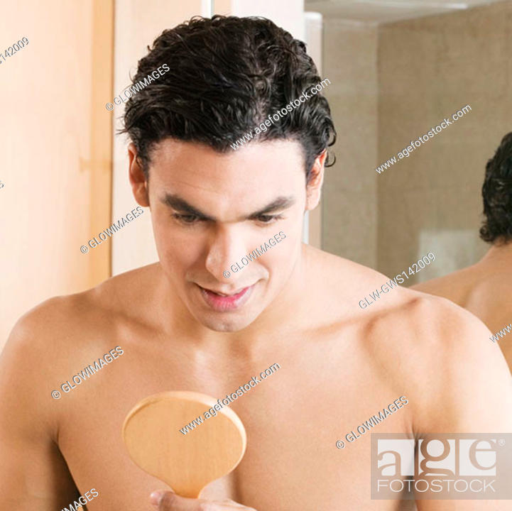 Stock Photo: Close-up of a young man looking into a mirror.