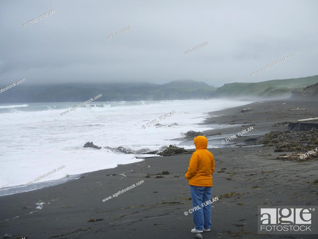 Stock Photo: Woman looking out to the storm tossed surf Kodiak Island, Alaska.
