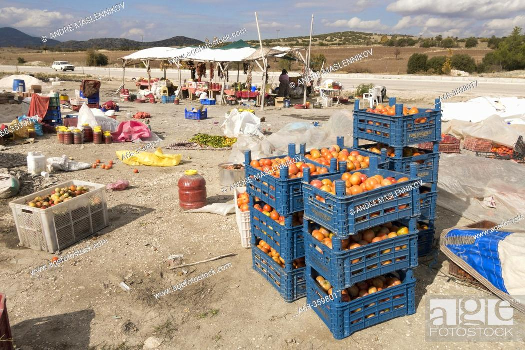 Stock Photo: A woman sells fresh, dried and pickled vegetables on the highway in Turkey.