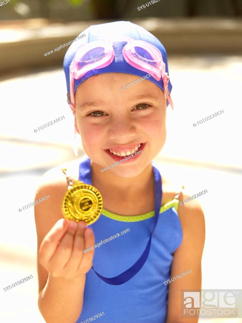 Stock Photo: Girl in swimming costume holding medal portrait.
