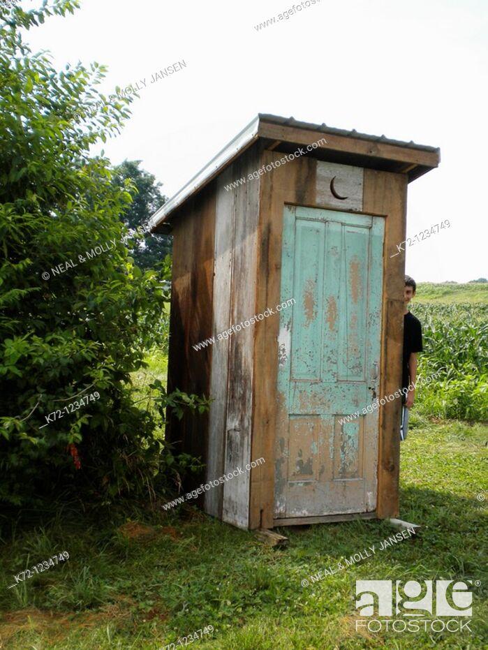 Stock Photo: Boy Peeking Around Outhouse.