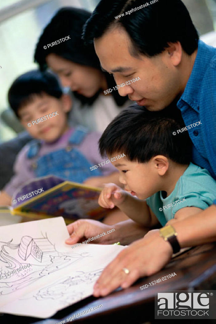 Stock Photo: Parents watching their two sons coloring with crayons.