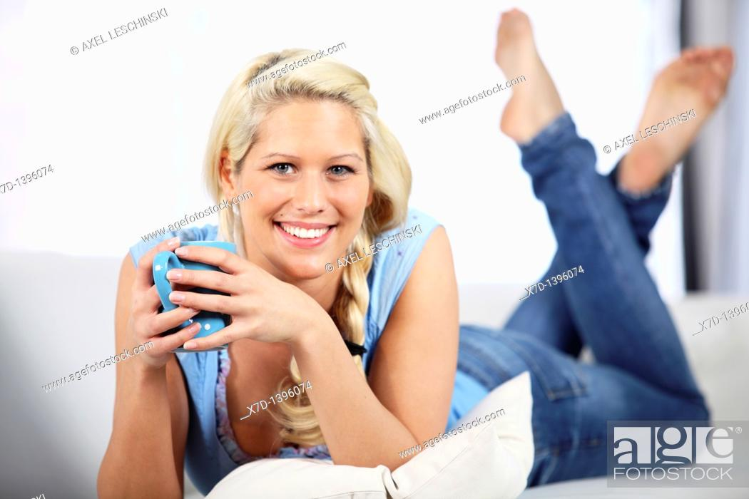Stock Photo: blond woman relaxing on sofa.