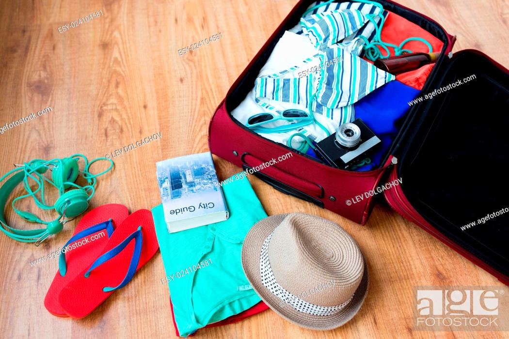 Stock Photo: summer vacation, travel, tourism and objects concept - close up of travel bag with clothes and stuff.