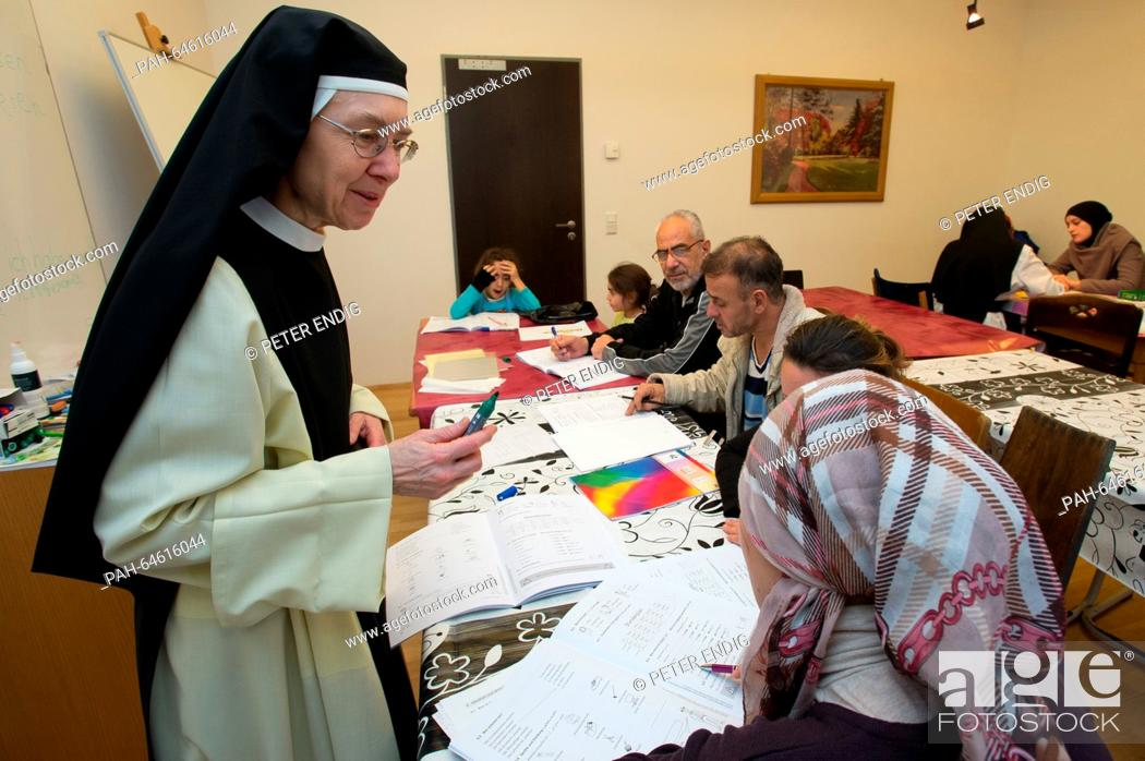 Stock Photo: Sister Katharina Gutlederer (L) assists Syrian refugess during a German language course in the Cistercienserinnen Monastery St.