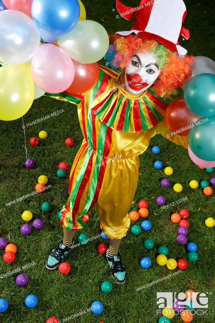 Imagen: Clown holding balloons on lawn.