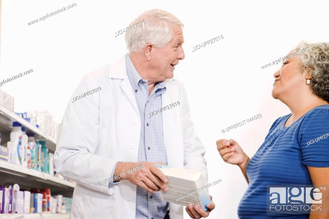 Stock Photo: Pharmacist helping customer with over-the-counter product.