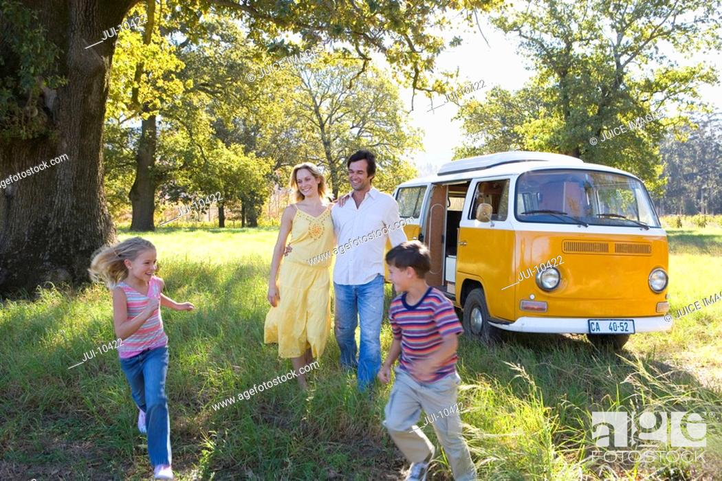 Stock Photo: Family of four in field by camper van, son and daughter running 5-9, smiling.