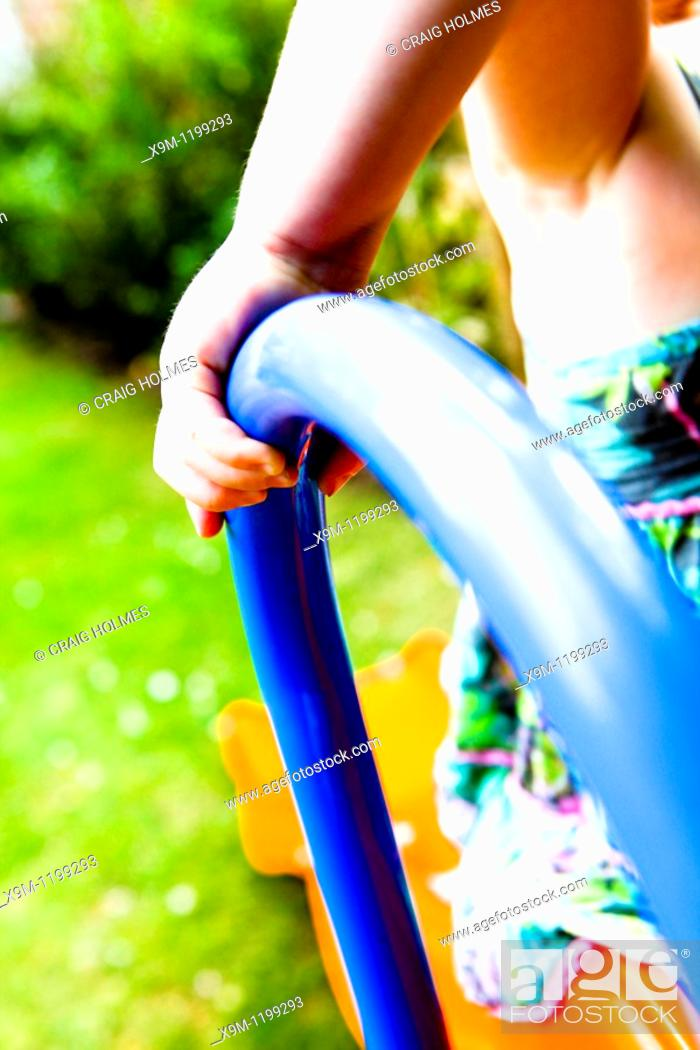 Stock Photo: A four year old girl plays on a slide in a garden.