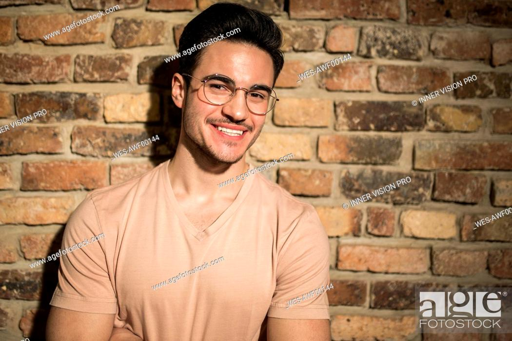 Stock Photo: Portrait of smiling young man at brick wall.