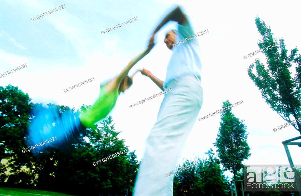 Stock Photo: Mature adult swinging a young girl.