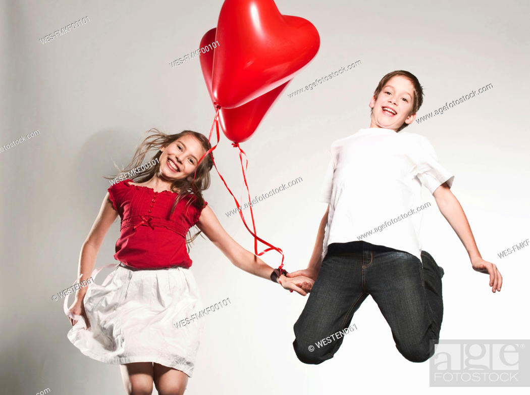 Stock Photo: Children 10-13 holding balloons and jumping, smiling, portrait.