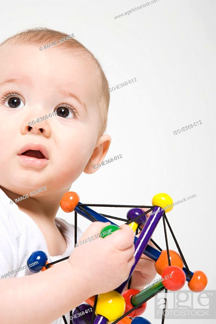 Stock Photo: A baby boy holding a toy.
