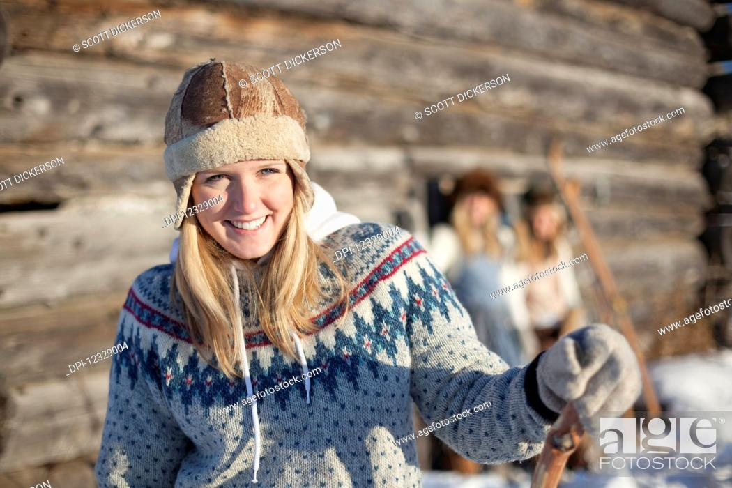 Photo de stock: Portrait Of A Young Woman Wearing A Hat And Sweater By A Log Cabin In Winter; Homer, Alaska, United States Of America.