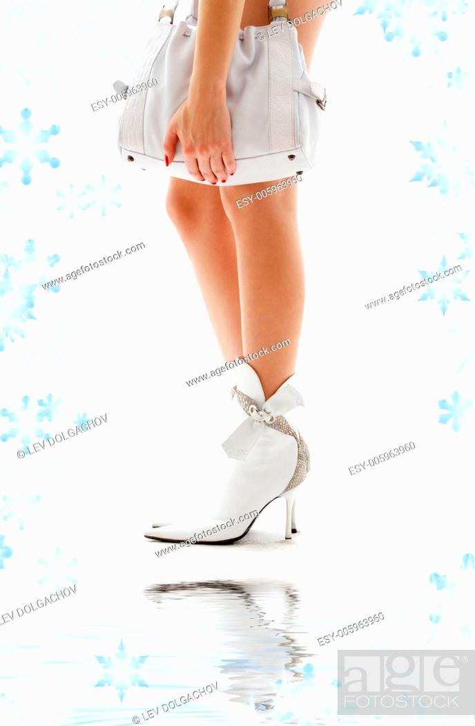 Stock Photo: closeup of beautiful legs in white boots with purse.