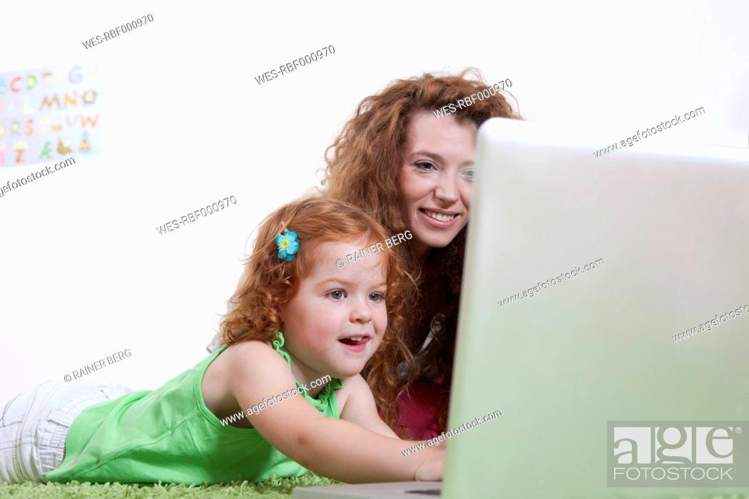 Stock Photo: Germany, Berlin, Mother and daughter using laptop on floor.