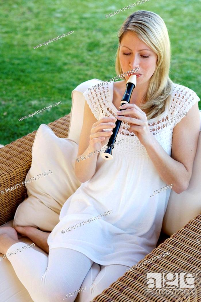 Stock Photo: Woman playing the flute in the terrace.